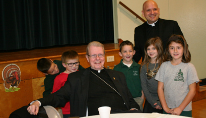 NOT CHRISTMAS YET: Bishop Scharfenberger joins Rev. Anthony Ligato, pastor of St. Jude the Apostle parish in Wynantskill, and the St. Jude School community for its annual Thanksgiving luncheon.