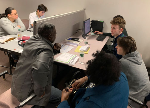 Catholic Central students (at r.) Nikko Peluso, Jack Simple and Derrick Anderson (behind Simple) help Uriel and Florence Huntley with tax prep, while Nick Farley (at l.) assists Crystal Hodge. (Franchesa Caputo photo)