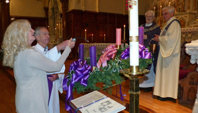HOLY FAMILY PARISH in Little Falls marks the first week of Advent with the lighting of an Advent wreath. Teresa Lee does the honors, assisted by administrator Deacon James Bower, as sacramental minister Rev. Terence Healy and Deacon Joseph DeLorenzo look on.