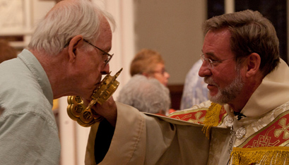 Father Bielecki holds a relic of St. Anne for a Mass-goer to kiss. (Nate Whitchurch photo)