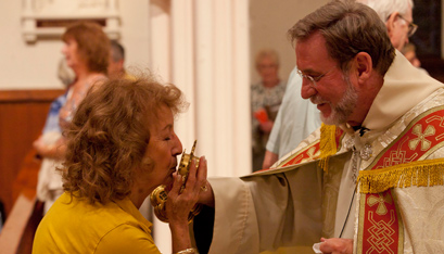 Father Bielecki holds a relic of St. Anne for Lucile Johnson to kiss. (Nate Whitchurch photo)