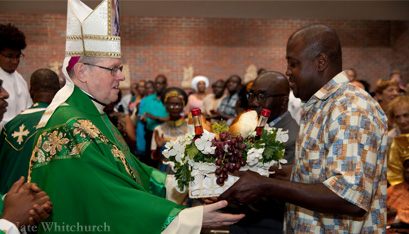 The Bishop accepts the offertory gifts from Rachidi Seidou-Bakari. (Nate Whitchurch photos)