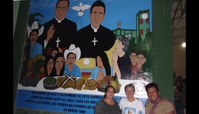 Peg Vámosy, center, with friends in front of a St. Romero mural that parish youth painted on the church in Monte San Juan.
