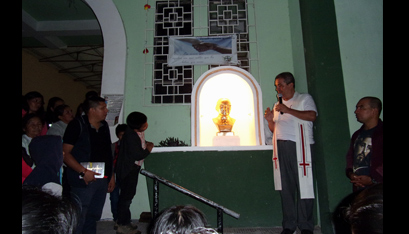 Father Mauricio, pastor, blesses a new bust of Romero at the Monte San Juan church entrance.